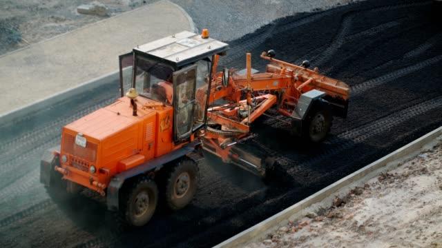 straßenarbeiten mit einem asphaltpflaster. spezielle straßenausrüstung. - asphalt stock-videos und b-roll-filmmaterial