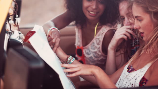 Road-tripping Afro girl and friend checking directions on a map video