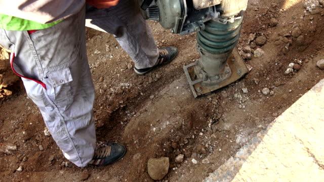 roadwork worker operating heavy gravel compacting machine video