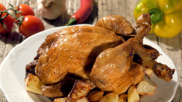 roast chicken with baked potatoes on white plate rotating video