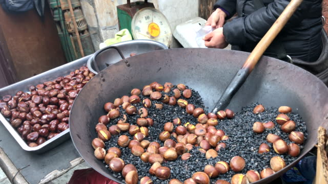 Roast Chinese chestnuts in big pan , Beijing , China. video