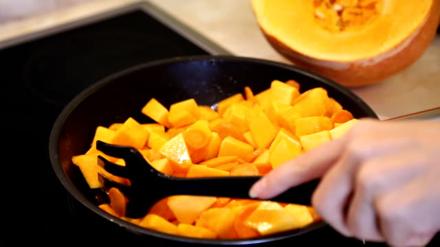 roast the carrots and pumpkin in a frying pan - zucca video stock e b–roll