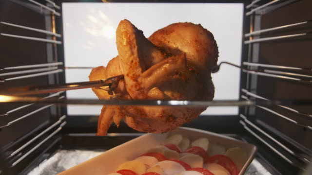 Roast whole chicken on the rotisserie spit in hot convection oven timelapse video