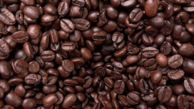 vidéos et rushes de grains de café arabica torréfiés se déplaçant vers le bas (2 clips) - entonnoir