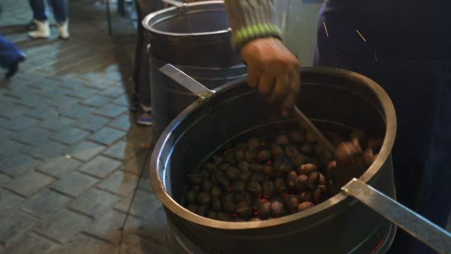 Roasted chestnuts at winter in the street. Video of a human hand roasting chestnuts at winter in the street. roasted stock videos & royalty-free footage
