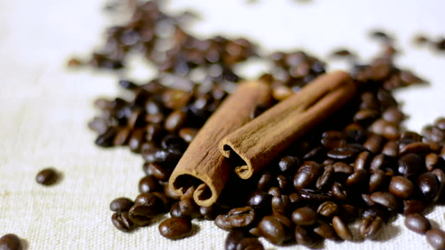 Roasted coffee beans and cinnamon sticks and falling coffee beans video