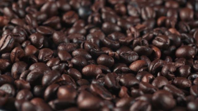 geröstete kaffeebohnen hintergrund, aus nächster nähe. duftende kaffeekörner rotierend - koffeinmolekül stock-videos und b-roll-filmmaterial