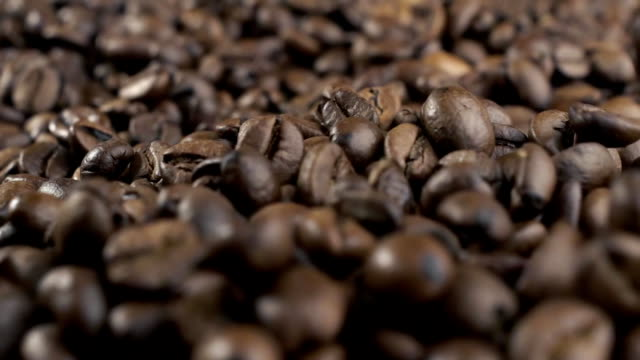 Roasted coffee beans falling down. Slow motion. Close-up shot video