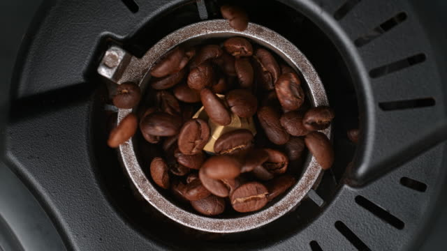 vídeos de stock e filmes b-roll de roasted coffee beans falling into the grinder and being crushed - triturar atividade