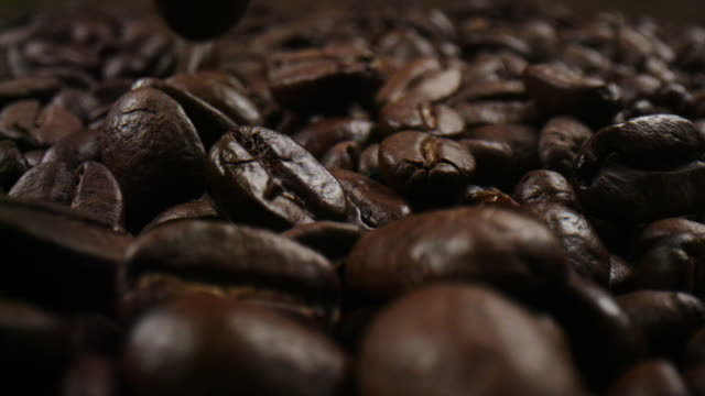 Roasted coffee beans in a macro shot in slowmotion