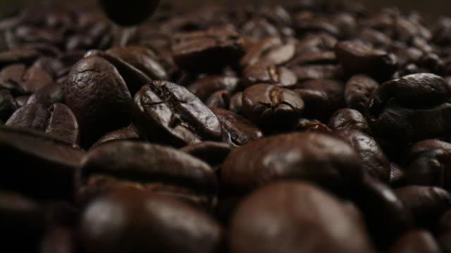 roasted coffee beans in a macro shot in slowmotion - espresso filmów i materiałów b-roll