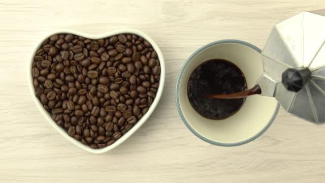 geröstete kaffeebohnen in herzform mit kaffeetasse - schwarzer kaffee stock-videos und b-roll-filmmaterial