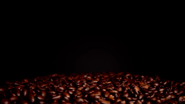 Roasted coffee beans rotate on black background. video