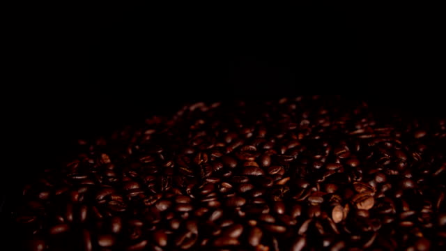 Roasted coffee beans rotate on black background.