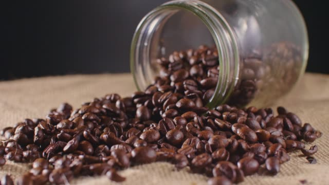 Roasted Coffee Beans Spilled From Jar On Hessian Sack 4K video