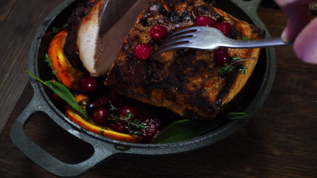 Roasted pork Roasted glazed pork with orange and cranberries. Cutting a slice of meat. Crane shot pork stock videos & royalty-free footage