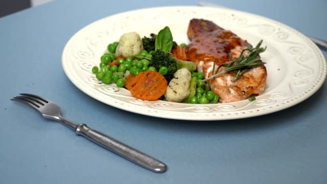 Roasted Pork with sauce, side by side on a plate of vegetable garnish of peas, carrots, broccoli and sea cabbage video