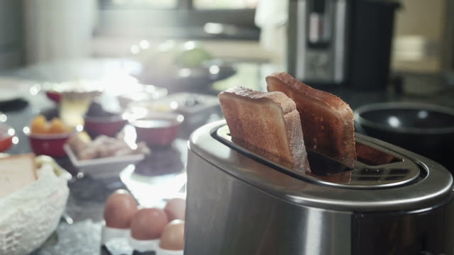 Roasted toast bread popping up from toaster slow motion video