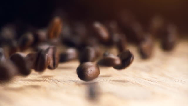 Roasting brown Coffee Beans with steam. tracking shot, close up - super slow motion. beans falling on wooden table