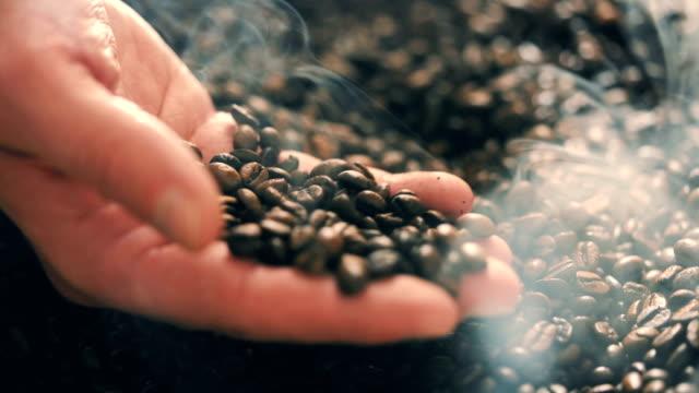 rösten braunen kaffeebohnen mit dampf. kamerafahrt, nahaufnahme - duftend stock-videos und b-roll-filmmaterial