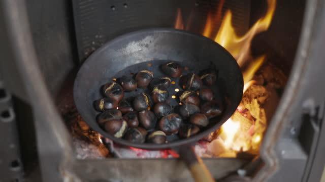 castagne arrosto in cast iron pan su open fire - marrone video stock e b–roll
