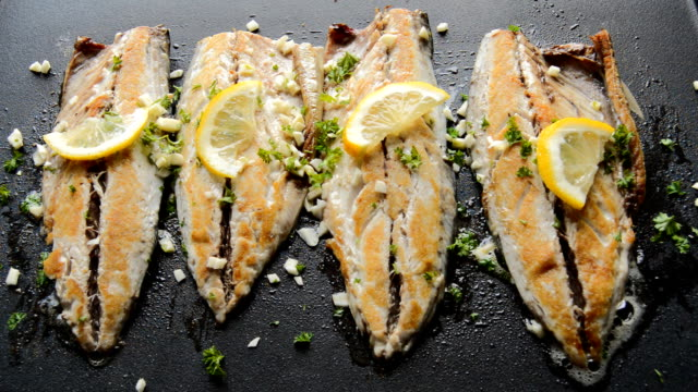 roasting fish on a pan with condiments and lemon - tillagad bildbanksvideor och videomaterial från bakom kulisserna