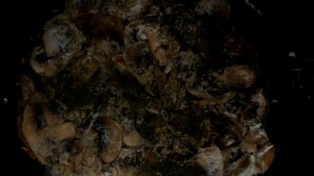 knoblauchpilze und champignon-pilze auf einer alten gusseisernen pfanne braten - speisepilz pilz stock-videos und b-roll-filmmaterial