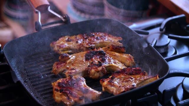 vidéos et rushes de torréfaction agneau côtelettes dans une grille de cuisson pan - ardoise