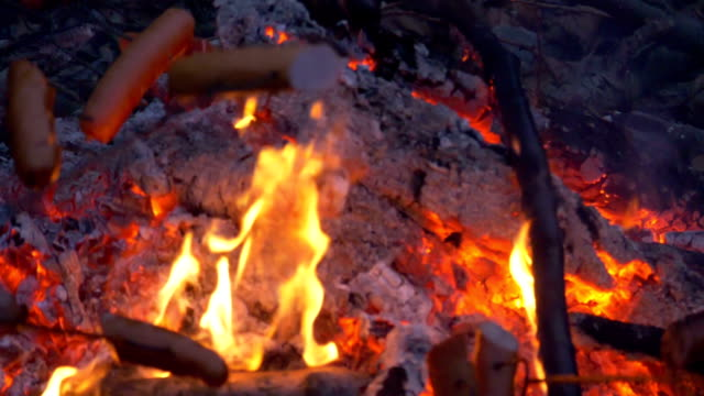 Roasting sausages on the bonfire in slow motion 180fps