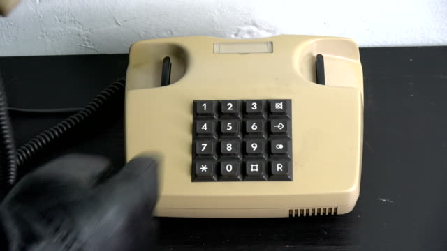 robber gangster hand with black leather glove pressing numbers buttons on classic  telephone - hand holding phone filmów i materiałów b-roll