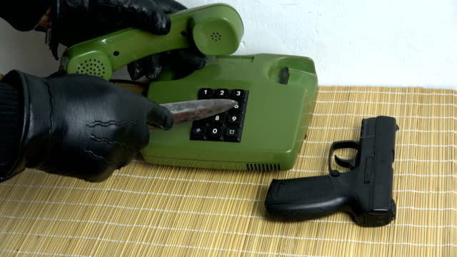 robber gangster hand with glove and dagger gun  pressing numbers buttons on retro telephone - hand holding phone стоковые видео и кадры b-roll