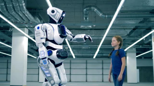 ロボットと手に触れる少女、側面図。学校の子供、教育、理科のクラスの概念。 - ai点の映像素材/bロール