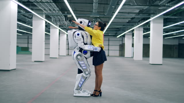 vídeos de stock e filmes b-roll de robot and woman hugging each other, standing in an empty room. - future hug