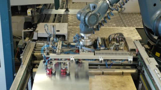 robot arm in a metal factory picks up metal plates - inarcare la schiena video stock e b–roll