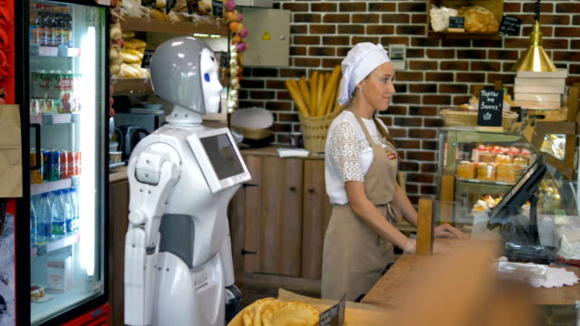 A robot helps a sales girl in a bakery. A white robot works beside a female worker in a bakery. robot stock videos & royalty-free footage