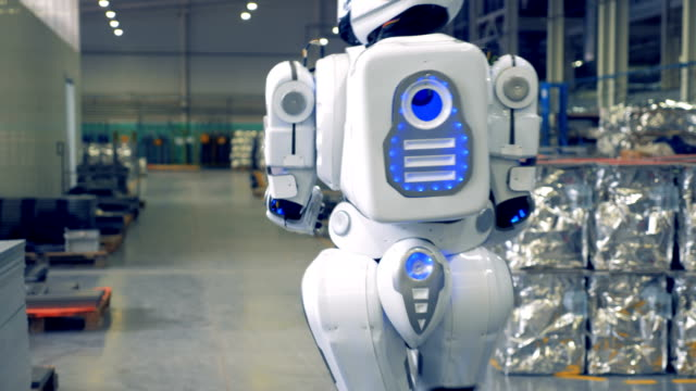 robot is walking through the factory facility from backside view - rivoluzione industriale video stock e b–roll