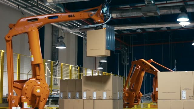 a robot lifting packing with products - automatico video stock e b–roll
