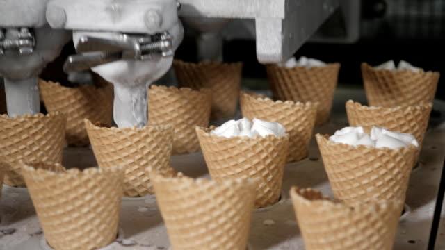 roboter-maschine gießt automatisch eis in ein wafer-cups. die automatische förderstrecken für die herstellung von eiscreme-kegel. wafer-cups und zapfen. große industrielle produktion. - gefrierkost stock-videos und b-roll-filmmaterial