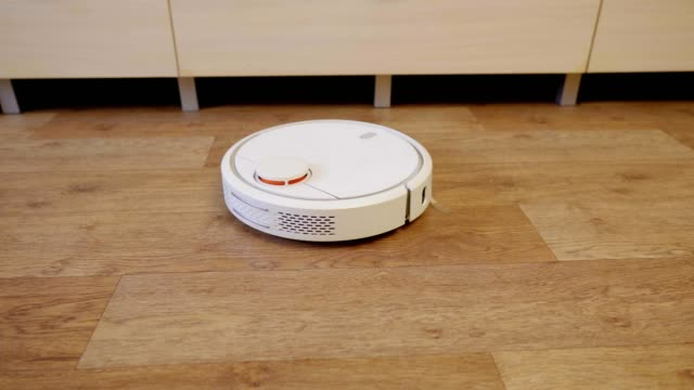robot vacuum cleaner on a wooden floor in a room - ассистент стоковые видео и кадры b-roll
