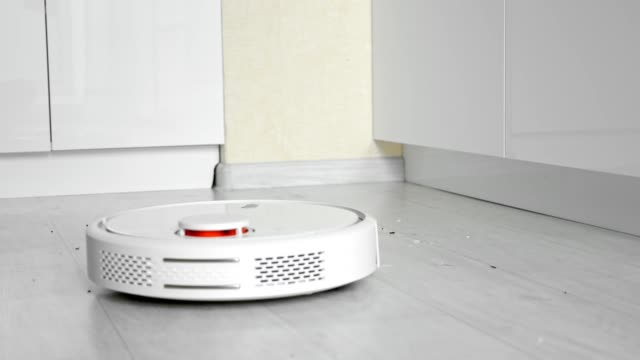 Robot vacuum cleaner with brushes removes garbage from floor Contemporary round automatic robot vacuum cleaner with brushes removes scattered garbage from wooden floor in brightly lit room closeup cordless phone stock videos & royalty-free footage