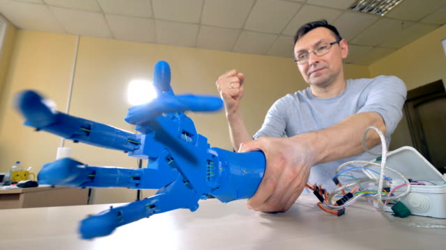 A robotic arm connected to laptop with many wires. An engineer programs bionic hand movements when it's connected to a laptop. prosthetic equipment stock videos & royalty-free footage