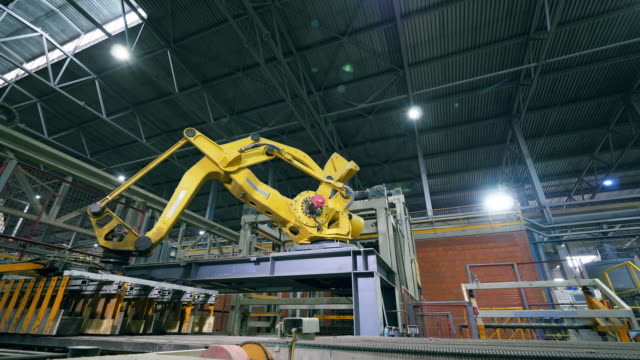Robotic Arm production line at a modern factory line. Mechanical loading machine is displacing ceramic products. 4K robot arm stock videos & royalty-free footage