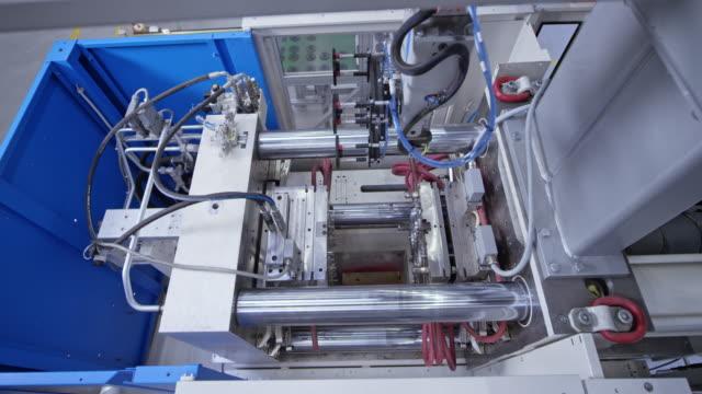 ld braccio robotico che toglie i prodotti in plastica dalla macchina di stampaggio - metal robot in logistic factory video stock e b–roll