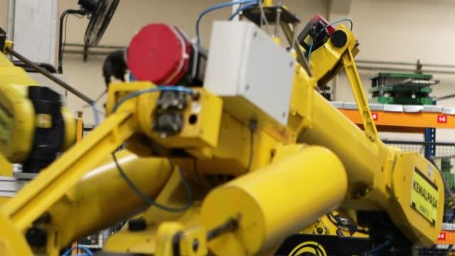 robotic arms in a factory - манипулятор робота производственное оборудование стоковые видео и кадры b-roll
