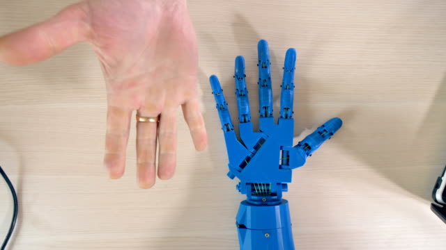 Robotic hand repeating man's right hand movements. Close up high angle of the bionic blue hand repeating man's right hand movements. robot arm stock videos & royalty-free footage