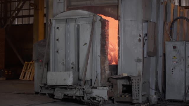 Robotic retractable furnace with red-hot metal workpieces in foundry. Room for manufacture of metal products by casting. Casting shop for gassified models. Heavy industry concept - vídeo