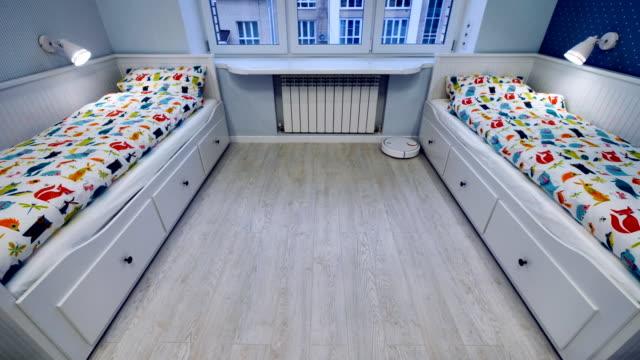 ein roboter vakuum bewegt sich entlang schlafzimmer wände und möbel. - waschmaschine wand stock-videos und b-roll-filmmaterial