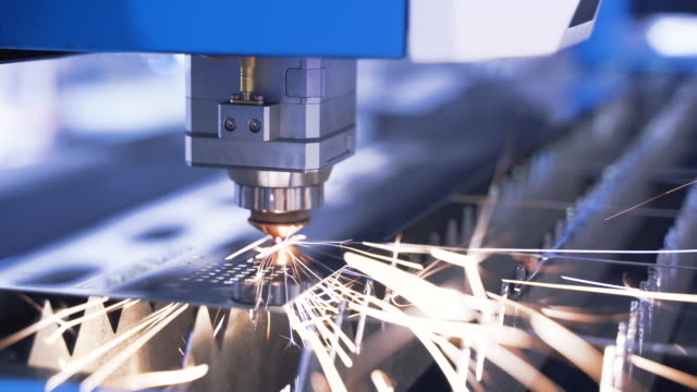 Robotics and engineering. Industrial machine CNC plasma laser cutter indoors. Bright sparks. Automation of sheet metal cutting process. Modern tool in industry. Computer control of high tech manufacture of construction product. Close-up. Slow motion
