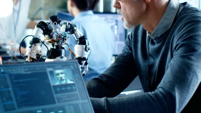 robotics engineer manipulates voice controlled robot, laptop screen shows speech and face reconizing software. in the background robotics reseatch center laboratory. - манипулятор робота производственное оборудование стоковые видео и кадры b-roll