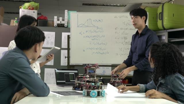 現代実験室におけるロボティクスチームミーティングと共同開発ロボットハードウェア技術、ロボット工学、人工知能と自動化制御の概念。4k 解像度。 - 機械工点の映像素材/bロール